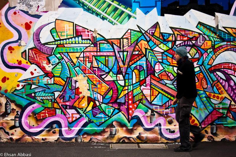 A man walks past graffiti